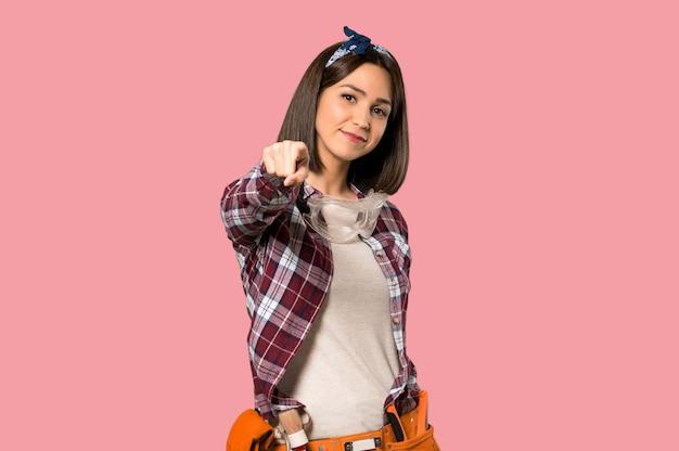 Jeune ouvrière femme pointe le doigt vers vous avec une expression confiante sur mur rose isolé