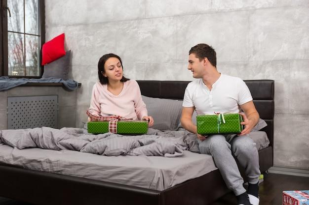 Une jeune paire en pyjama considère les cadeaux de l'autre tout en étant assis sur le lit dans la chambre de style loft le matin de noël