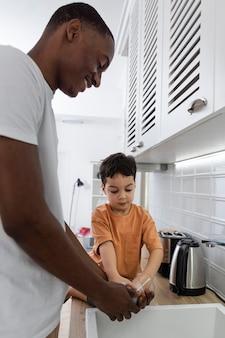 Jeune papa lave la vaisselle avec son fils