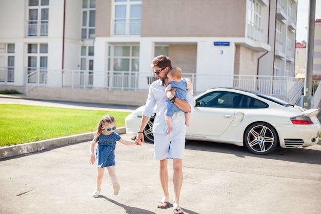 Jeune papa marche avec ses deux filles sur le fond d'une voiture de sport