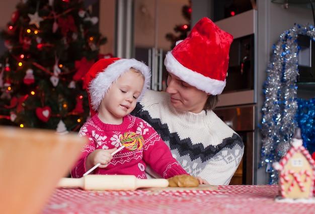 Jeune papa et petite fille au bonnet de noel cuire des biscuits de pain d'épice de noël