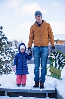Jeune papa et petite fille vont faire de la luge dans une froide journée d'hiver
