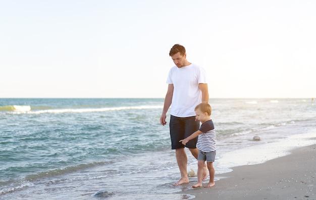 Jeune papa de race blanche avec petit fils à pied chaude journée d'été le long de la côte de la mer