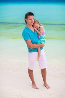 Jeune papa et sa petite fille marchant sur la plage de sable blanc tropicale