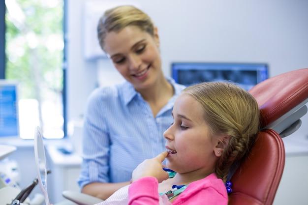 Jeune patient regardant dans le miroir à la clinique dentaire
