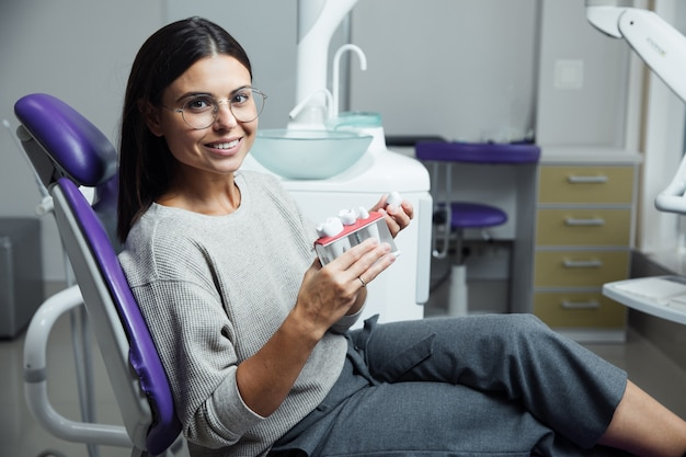 Jeune patiente assise sur une chaise en cabinet dentaire.