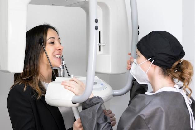Jeune patiente debout dans la machine à rayons x.