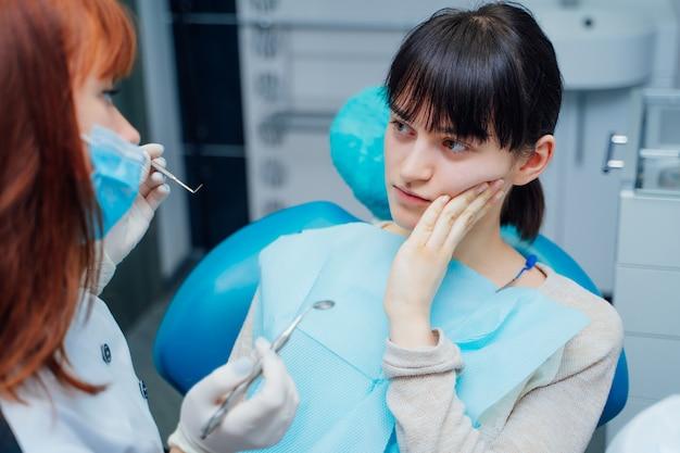 Jeune patiente montre le dentiste à ses douleurs dentaires en stomatologie.