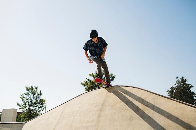 Jeune patineur au sommet de la demi-pipe