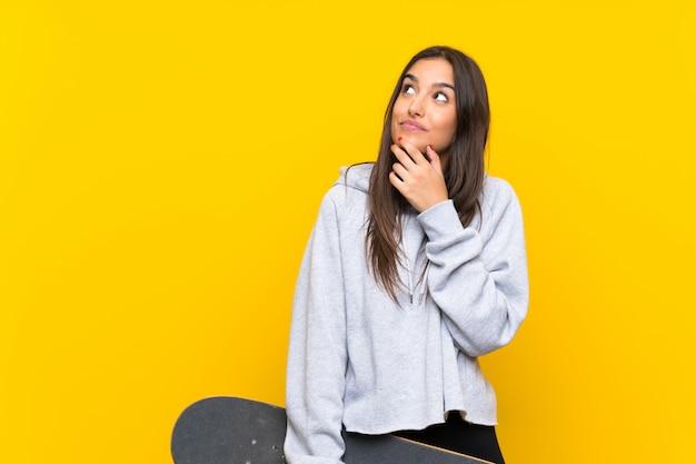 Jeune patineur femme sur mur jaune isolé, pensant une idée