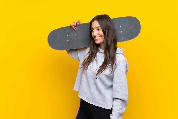 Jeune patineur femme sur mur jaune isolé