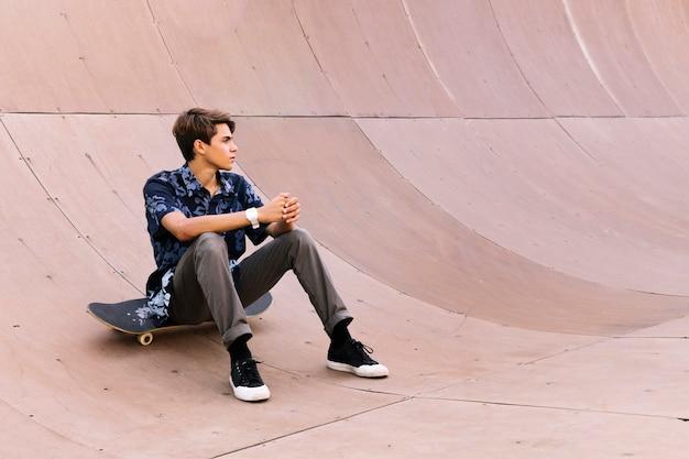 Jeune patineur garçon assis en demi-pipe