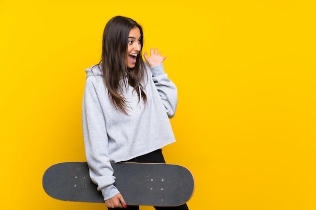 Jeune patineuse femme isolée sur jaune avec une expression faciale surprise