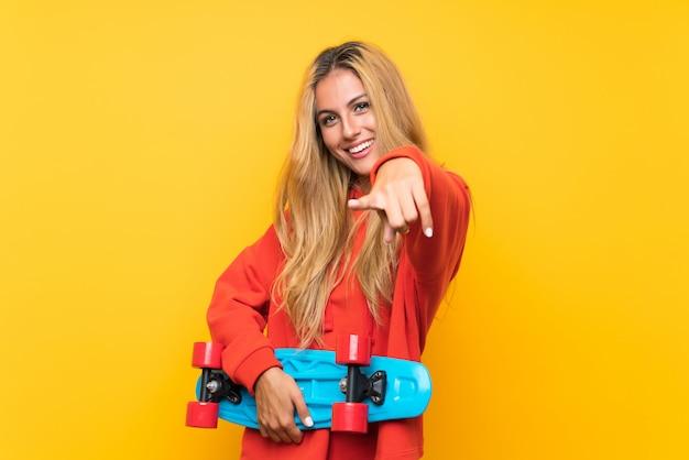 Jeune patineuse femme pointant vers l'avant sur un mur jaune isolé