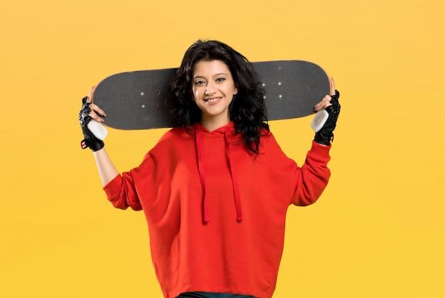 Jeune patineuse femme avec un sweat-shirt rouge