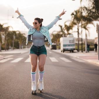 Jeune patineuse levant les bras en faisant le geste de la paix en équilibre sur la route