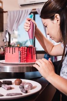 Jeune pâtissière professionnelle décorant un gâteau coloré.