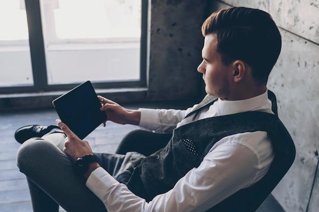 Jeune patron confiant vérifiant le travail de son employé sur une tablette assis sur une chaise dans son bureau contre une grande fenêtre.
