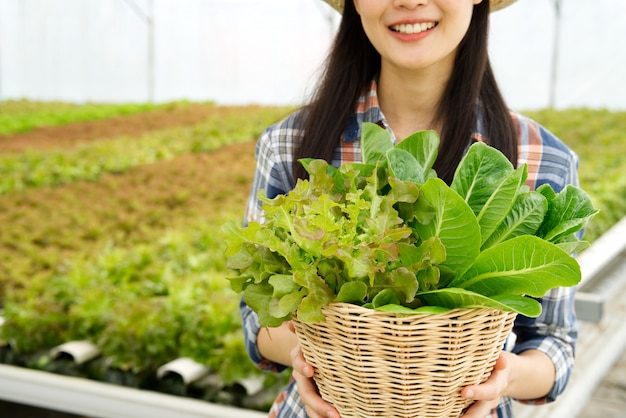 Jeune paysanne fille tenant un panier de légumes dans une ferme hydroponique avec sourire