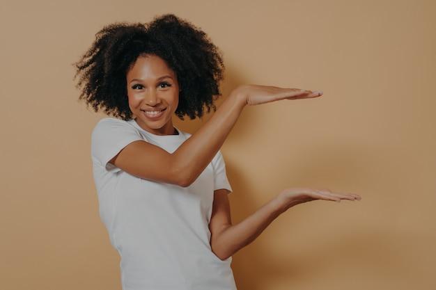 Jeune peau foncée montrant un grand objet, façonnant une boîte avec les deux mains, isolée sur fond beige
