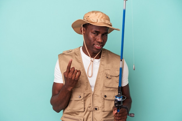 Jeune pêcheur afro-américain tenant une tige isolée sur fond bleu pointant le doigt vers vous comme s'il vous invitait à vous rapprocher.