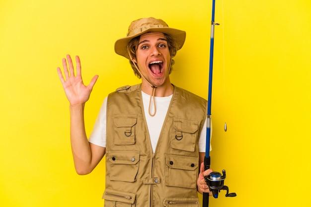 Jeune pêcheur au maquillage tenant une tige isolée sur fond jaune recevant une agréable surprise, excité et levant les mains.