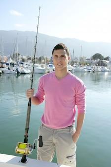 Jeune pêcheur de bateau pêcheur avec canne et moulinet