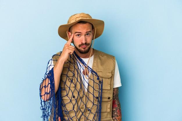 Jeune pêcheur caucasien avec des tatouages tenant un filet isolé sur fond bleu pointant le temple avec le doigt, pensant, concentré sur une tâche.