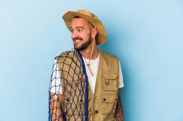 Jeune pêcheur caucasien avec des tatouages tenant un filet isolé sur fond bleu regarde de côté souriant, joyeux et agréable.
