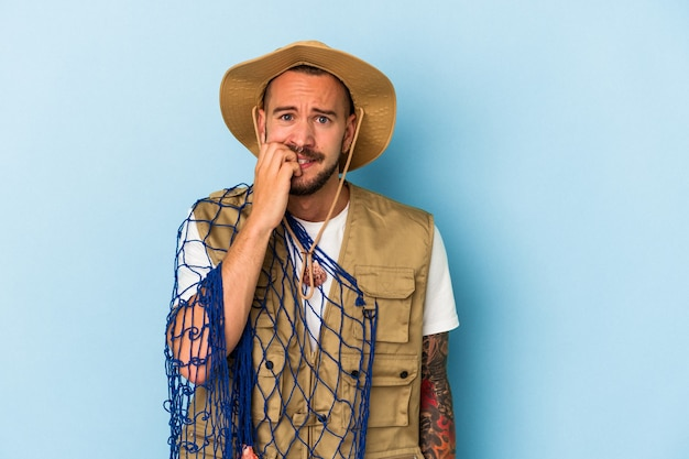 Jeune pêcheur caucasien avec des tatouages tenant un filet isolé sur fond bleu se rongeant les ongles, nerveux et très anxieux.