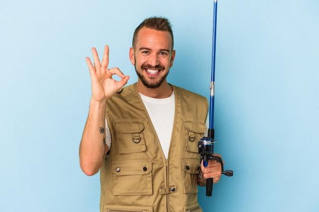 Jeune pêcheur caucasien avec des tatouages tenant une tige isolée sur fond bleu joyeux et confiant montrant un geste correct.