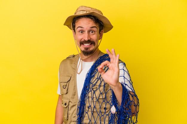 Jeune pêcheur caucasien tenant un filet isolé sur fond jaune joyeux et confiant montrant un geste correct.