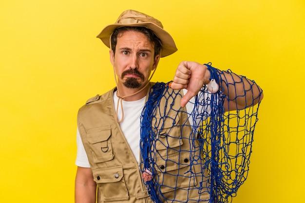 Jeune pêcheur caucasien tenant un filet isolé sur fond jaune montrant un geste d'aversion, les pouces vers le bas. notion de désaccord.