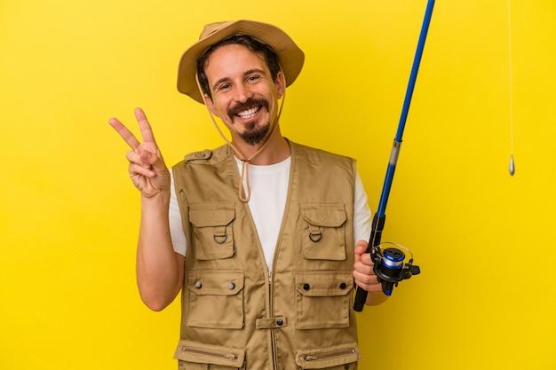 Jeune pêcheur caucasien tenant une tige isolée sur fond jaune joyeux et insouciant montrant un symbole de paix avec les doigts.