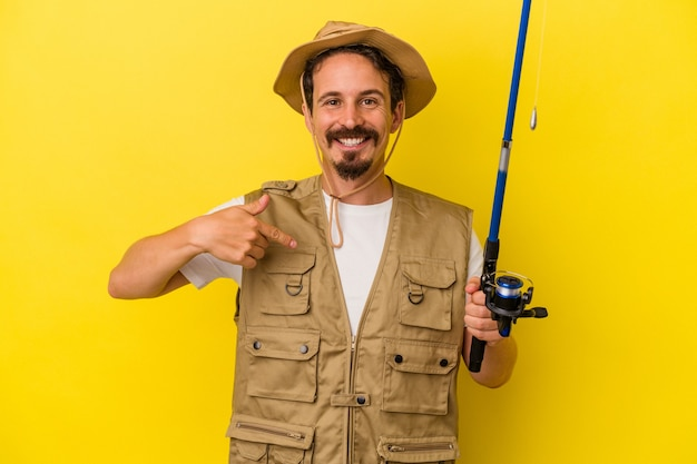 Jeune pêcheur caucasien tenant une tige isolée sur fond jaune personne pointant à la main vers un espace de copie de chemise, fier et confiant