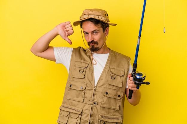 Jeune pêcheur caucasien tenant une tige isolée sur fond jaune se sent fier et confiant, exemple à suivre.