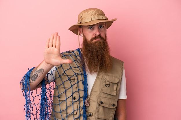 Jeune pêcheur de gingembre caucasien avec longue barbe tenant un filet isolé sur fond rose