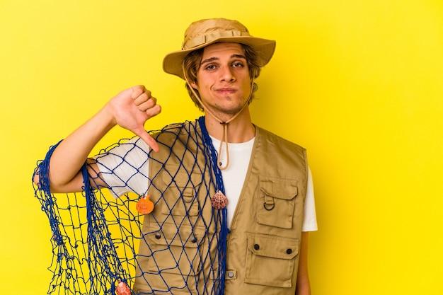 Jeune pêcheur maquillé tenant un filet isolé sur fond jaune montrant un geste d'aversion, les pouces vers le bas. notion de désaccord.