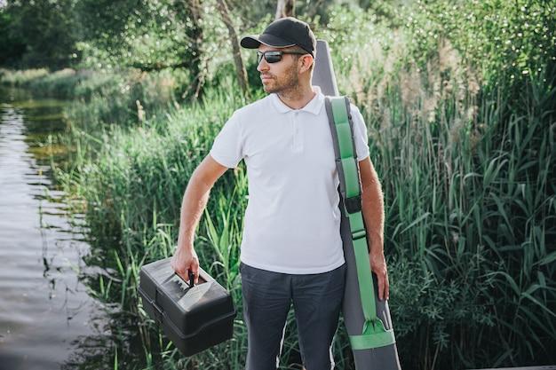 Jeune pêcheur pêchant sur lac ou rivière. cool guy confiant occupé marchant avec du matériel de pêche au bord de l'eau. emportez des cannes, des leurres et des moulinets pour son passe-temps de chasse à l'eau.