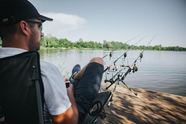 Jeune pêcheur pêchant sur lac ou rivière. guy assis dans une chaise pliante et regardant droit devant le lac ou la rivière. trois cannes à pêche devant lui pour obtenir du poisson frais. chasse à l'eau.