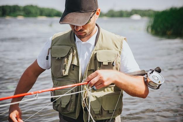 Jeune pêcheur pêchant sur lac ou rivière. guy sérieux concentré occupé tenant la canne et la ligne de pêche dans les mains. se préparer à la pêche. guy se tient dans l'eau d'une rivière ou d'un lac.