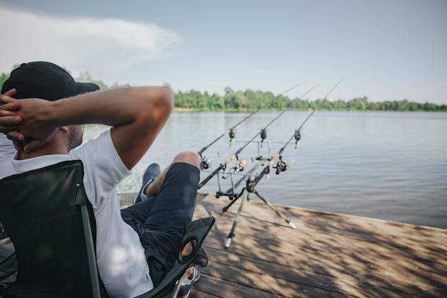 Jeune pêcheur pêchant sur lac ou rivière. homme adulte détendu assis dans une chaise pliante et en attente de poisson.