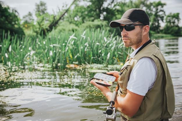 Jeune pêcheur pêchant sur lac ou rivière. mec cool et sérieux occupé en célibataires tenant des leurres en plastique de poisson dans une boîte avant de les utiliser pour attraper du poisson. restez seul dans l'eau.