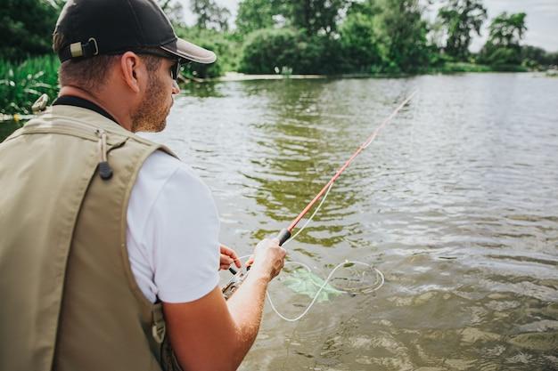Jeune pêcheur pêchant sur lac ou rivière. vue arrière du gars concentré en attente d'attraper du poisson. homme tenant une canne à pêche dans les mains. journée ensoleillée à la rivière ou au lac.