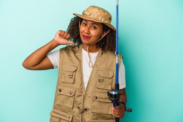 Jeune pêcheuse afro-américaine tenant une canne isolée sur fond bleu se sent fière et confiante, exemple à suivre.