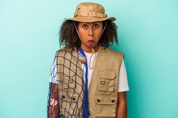 Jeune pêcheuse afro-américaine tenant un filet isolé sur fond bleu hausse les épaules et ouvre les yeux confus.