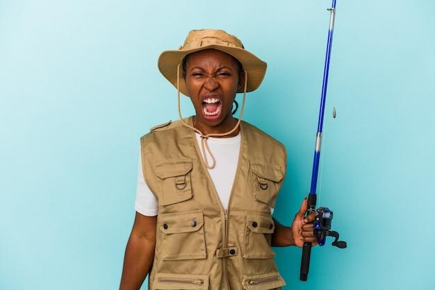 Jeune pêcheuse afro-américaine tenant une tige isolée sur fond bleu criant très en colère et agressive.