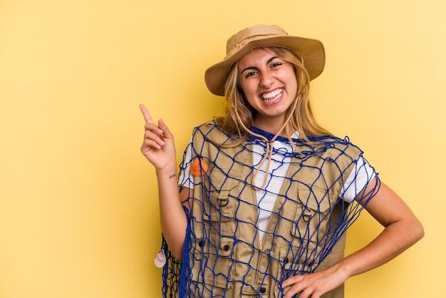 Jeune pêcheuse blonde caucasienne tenant une tige isolée sur fond jaune souriant et pointant de côté, montrant quelque chose dans un espace vide.