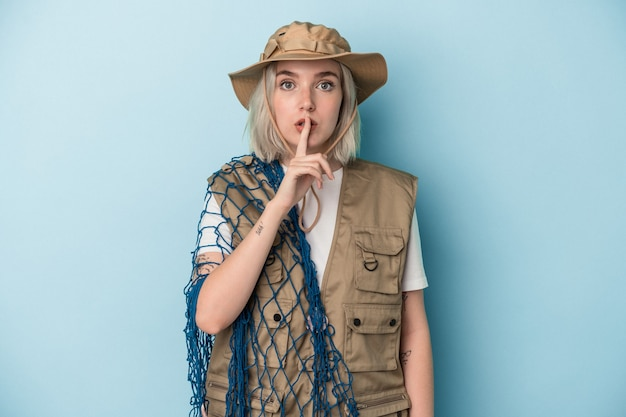 Jeune pêcheuse caucasienne tenant un filet isolé sur fond bleu gardant un secret ou demandant le silence.