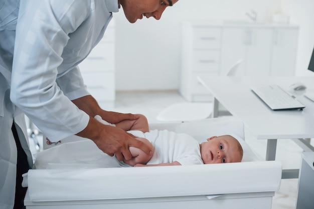 Le jeune pédiatre est avec le petit bébé dans la clinique pendant la journée.